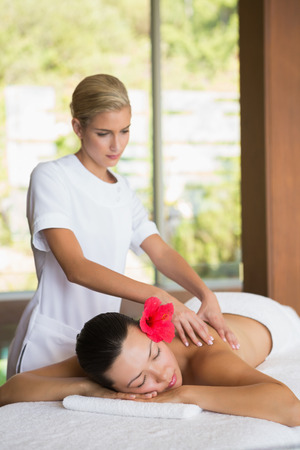 Brunette enjoying a peaceful massage at the health spa Stock Photo