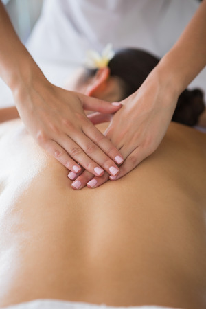 Brunette enjoying a back massage at the health spa
