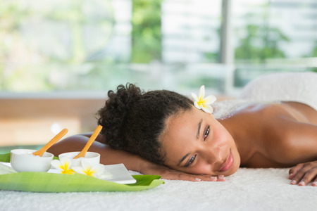 therapy room: Gorgeous woman lying on massage table with salt treatment on back at the health spa