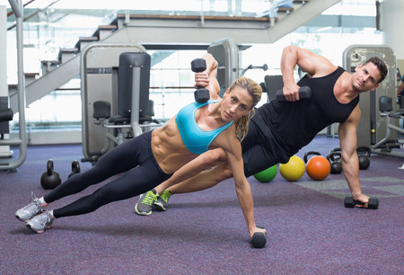 Bodybuilding man and woman holding dumbbells in plank position at the gym photo