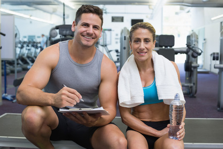 Female bodybuilder sitting with personal trainer smiling at camera at the gym photo