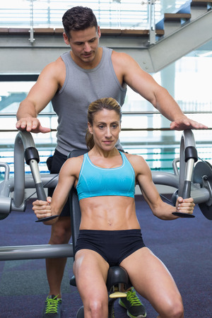 weight machine: Personal trainer coaching female bodybuilder using weight machine at the gym Stock Photo