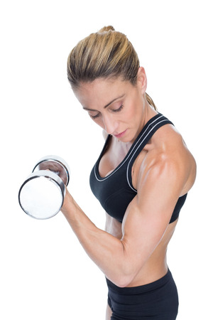 lean out: Female bodybuilder holding a large dumbbell looking at bicep on white background