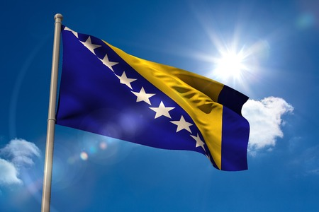 bosnian: Bosnian national flag on flagpole on blue sky background