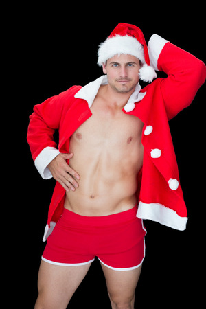 Muscular man posing in sexy santa outfit on black background photo