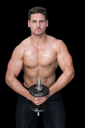Strong crossfitter lifting up heavy black dumbbell on black background photo
