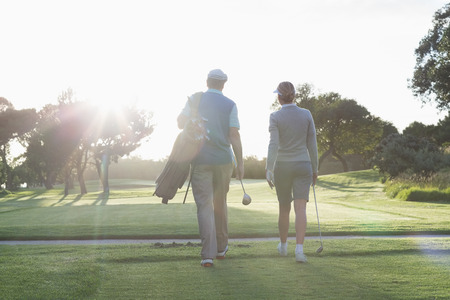 Golfing couple walking and chatting on a sunny day at the golf course photo