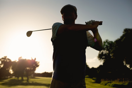 Golfer teeing off for the day on a sunny morning at the golf course photo