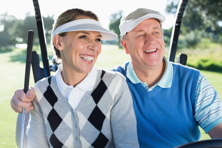 Happy golfing couple sitting in golf buggy smiling on a sunny day at the golf course photo