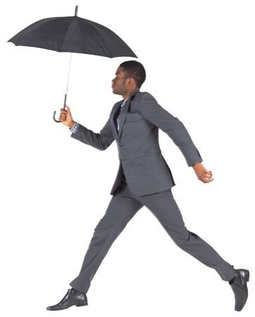 Businessman walking and holding umbrella on white background photo