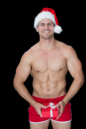 Smiling muscular man posing in sexy santa outfit holding gift on black background photo
