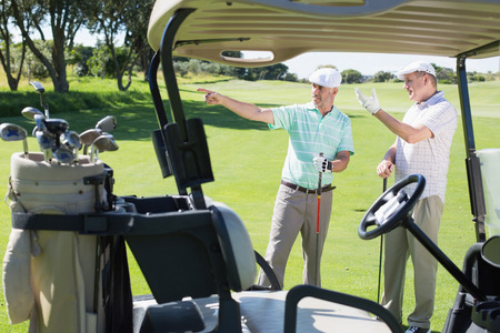 Golfing friends standing beside their buggy looking around on a sunny day at the golf course photo
