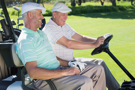 Golfing friends laughing together in their golf buggy on a sunny day at the golf course photo