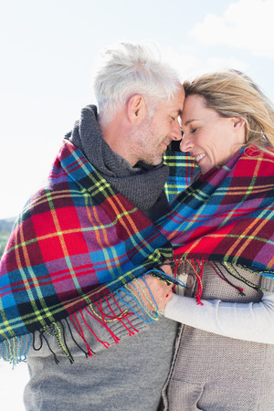 wrapped up: Happy couple wrapped up in blanket standing on the beach on a bright but cool day Stock Photo