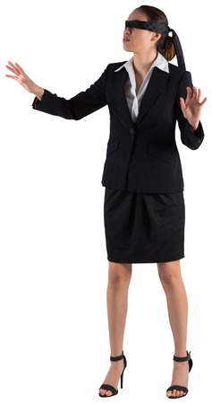 Blindfolded businesswoman with hands out on white background photo