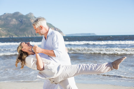 Happy couple dancing on the beach together on a sunny day photo