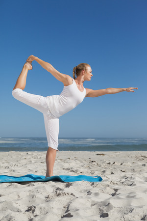 beach mat: Blonde woman standing in warrior pose on beach on a sunny day