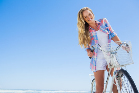 bike riding: Pretty blonde on a bike ride at the beach smiling at camera on a sunny day
