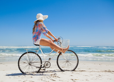 escapism: Pretty carefree blonde on a bike ride at the beach on a sunny day