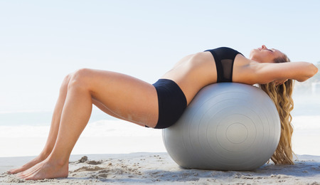 Fit blonde stretching her back on exercise ball at the beach on a sunny day photo