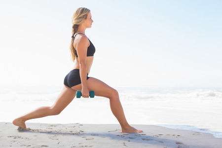 Fit blonde doing weighted lunges on the beach on a sunny day photo