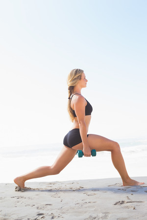 lunges: Fit blonde doing weighted lunges on the beach on a sunny day Stock Photo
