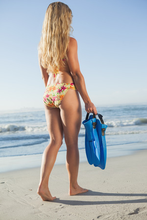 Woman holding flippers walking towards the sea on a sunny day photo
