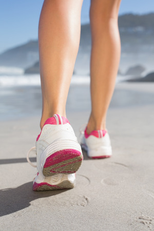 Fit woman walking on the beach on a sunny day photo