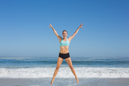 slender woman: Fit woman jumping on the beach with arms out on a sunny day