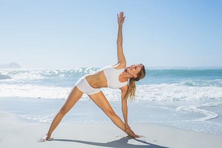 Gorgeous blonde standing in extended triangle pose by the sea on a sunny day