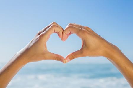 Vrouwelijke handen maken hartvorm door de zee op een zonnige dag Stockfoto