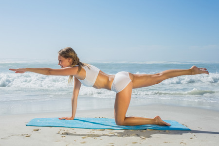 beach mat: Gorgeous fit blonde in pilates pose on the beach on a sunny day Stock Photo