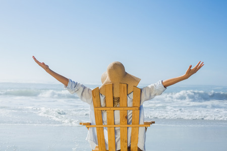 escapism: Woman relaxing in deck chair by the sea on a sunny day