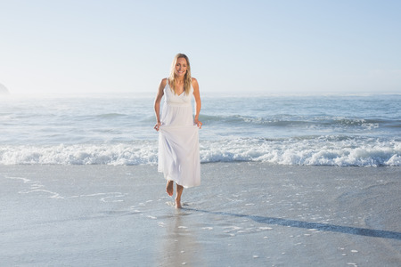 maxi dress: Pretty blonde at the beach in white sundress on a sunny day Stock Photo