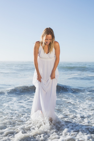 maxi dress: Pretty blonde standing in the sea at the beach in white sundress on a sunny day