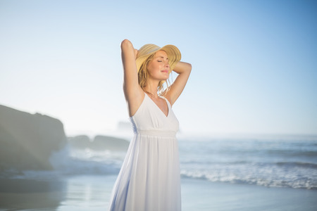 woman relaxing: Smiling blonde standing at the beach in white sundress and sunhat on a sunny day
