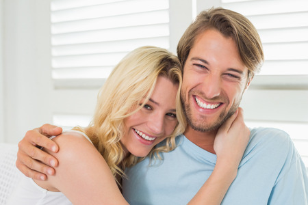 Cute casual couple sitting on couch laughing at camera at home in the living room photo