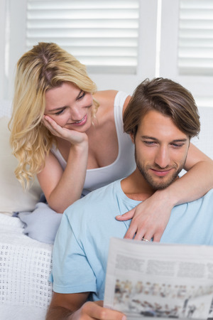 Happy casual couple sitting on couch reading newspaper together at home in the living room photo