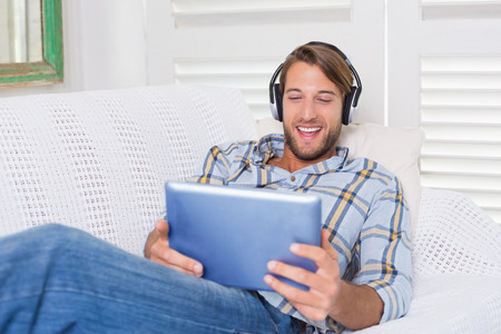 Casual smiling man lying on couch listening to music on tablet pc at home in the living room