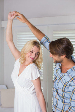 Cute young couple dancing together at home in the living room photo