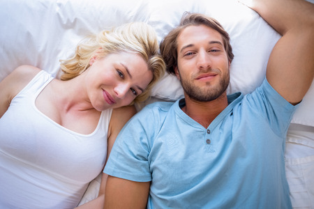 Cute couple relaxing on bed smiling at camera at home in the bedroom photo