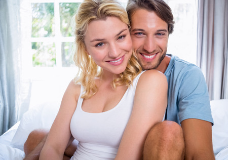 Cute young couple relaxing on bed smiling at camera at home in the bedroom photo