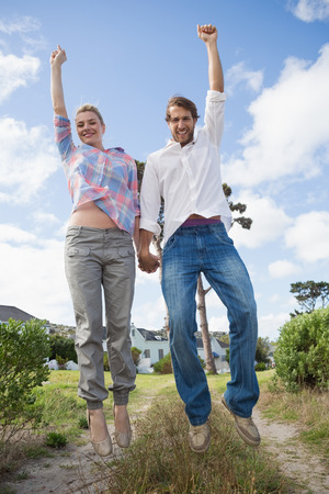 Smiling couple leaping outside together in their garden on a sunny day photo