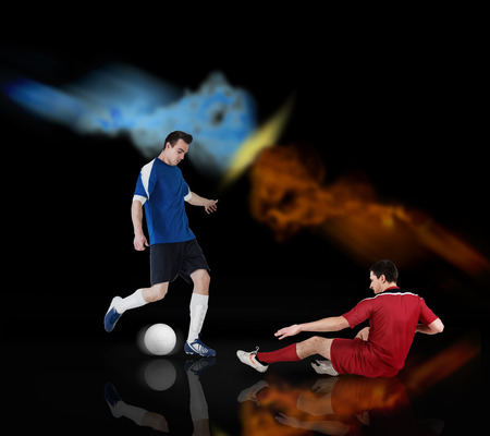Football players tackling for the ball on black background with lights Stock Photo - 29066952