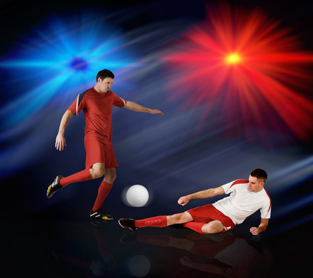 Football players tackling for the ball on black background with lights Stock Photo - 29066956