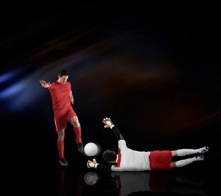 Football players tackling for the ball on black background with lights Stock Photo - 29066959