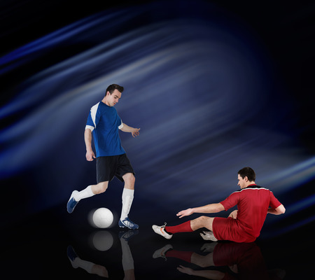 Football players tackling for the ball on black background with lights Stock Photo - 29066960