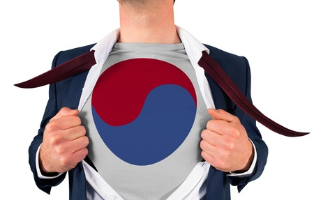 Businessman opening shirt to reveal korea republic flag on white background photo