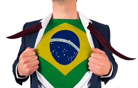 Businessman opening shirt to reveal brasil flag on white background photo