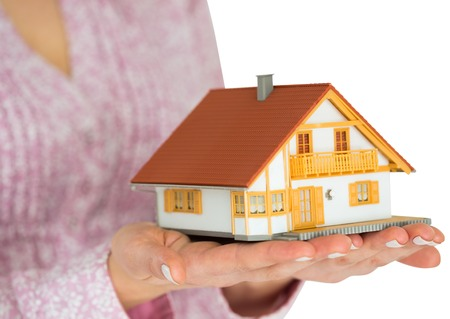 Hands showing a miniature model home on white background photo
